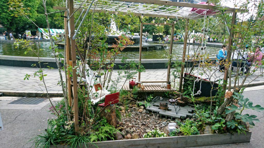 枝で作った椅子に座りテレワーク出来る場所とソロストーブを利用しコーヒー豆を焙煎する場所と上にはロープでのハンモックを設置した庭