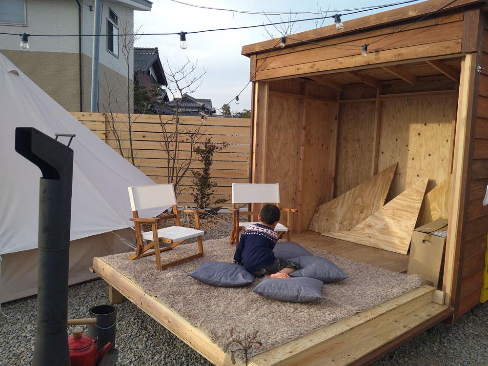 壁が全開閉する小屋で遊ぶ子供の写真